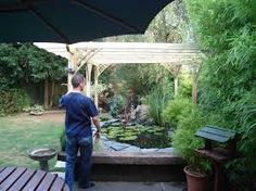 Pergola over pond koi ponds pinterest pergolas for Raised koi pond construction