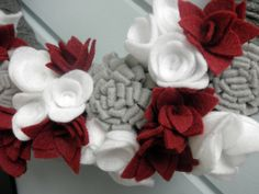 This wreath is wrapped in dark gray yarn with red, white, and light gray flowers, making it perfect for the holidays. It measures 14 inches, and hangs from a dark red satin ribbon. I love this wreath so much, Im making the same one for my house