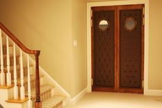Theater double swing door with tufted leather panel and mirrored porthole window.