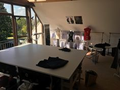 my new studio right after moving in. the large table is - beside the fabrics and the machines - the most important furniture in the room. i love the luxurious space for cutting, pattern making, pin tacking etc. and the light-flooded view into the garden is also very nice!!