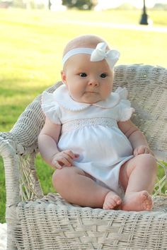 This is a delicate white and pink hand smocked baby girls bubble, in which your little girl will look absolutely beautiful! It has angel sleeves, a Peter Pan collar, and petite pink smocking on the edges. There are snaps on the bottom for easy on and off. Made of 100% Pima Cotton.