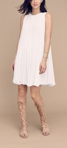 Crisp accordion pleats enhance the flyaway movement of this simple shift dress fashioned from fluid crepe. So cute!
