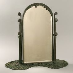 "Tiffany Studios ""Fern"" Table Mirror  A Tiffany Studios New York silvered glass and bronze ""Fern"" table mirror, featuring an elaborate and intricately pierced and sculpted patinated bronze base decorated with stylized fern leaves, c 1910"