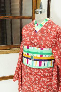 ほのかにスモークがかった朱赤地に、四季の草花が楚々と浮かび上がる縮緬の単着物です。 #kimono