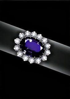 """El anillo de compromiso de zafiro y diamante  Creado por Garrards en 1980, el anillo consta de un zafiro de Ceylán de 12 quilates ovalado rodeado por 14 diamantes y montado en oro blanco de 18 quilates. La leyenda urbana dice que la princesa seleccionó este  anillo porque era """"el más grande"""" en una bandeja de anillos enviados por Garrards, pero la princesa  en una oportunidad dijo que el anillo fue seleccionado por la Reina y el Príncipe Carlos."""