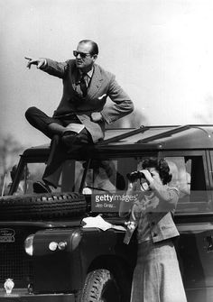 Prince Philip, Duke of Edinburgh seated on the roof of a Land Rover pointing out competitors at the Badminton Horse Trials to Queen Elizabeth II who is watching through binoculars. April 20, 1968