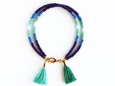 Blue double strand bracelet with two tassels: one in aqua and one in peacock green color. Details: - mix of glass seed beads, - handmade cotton tassels, - gold plated metal findings, - approx. 7.5 L All Felt Like Paper items arrive in muslin bags. If your order is a gift please