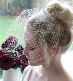 Straight out of the 1940s...  Vintage style, short birdcage veil with beaded appliqué and attached to a hair comb for an easy fit.  Hand beaded