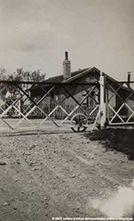 4| Photographie du passage à niveau de Nuisement-sur-Coole [Marne] et de la maison de Mme Lévêque, vers 1940. Le trafic de la ligne Châlons-Troyes sur laquelle était situé le passage à niveau de Nuisement-sur-Coole n'était pas très important. il était composé essentiellement de trains marchandises. Y circulaient également les trains de prisonniers de guerre, qui jetaient des petits mots en passant. Mme Lévêque les rassemblaient et les portaient au maire chaque soir.