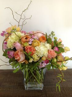 Green Bouquet Floral Design; flower arrangement  of white hydrangea, peach roses, peach ranunculus, pink roses, pink stock flowers, mint, pe...