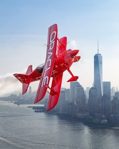 "emmanuelcanaan: ""Freedom Sean D. Tucker soars over the New York City skyline and the iconic Freedom tower in advance of the 2016 Bethpage Air Show at Jones Beach. """