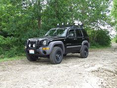 Really want to do this to mine!  jeep liberty- Brush guard with off road lights, offroad wheels & tires, roof rack with off road lights