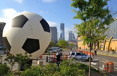 Our giant soccer ball inflatable balloon with our Feather Banners on the right and the new Freedom Tower in the back ground