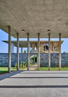 A rugged wall made from locally sourced grey stone separates this block from a large pavilion, which serves as an events space for the local community. Materials And Structures, Outdoor Structures, Stone Wall Design, Floating Staircase, Concrete Houses, The Embrace, Artistic Installation, Ground Floor Plan, Tropical Landscaping