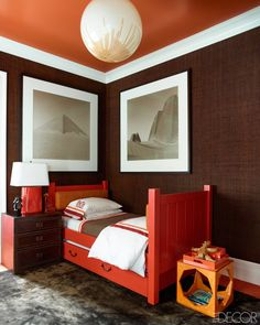 "Gambrel points to the table in the dining room and the stove in the kitchen—both bright orange—as further examples of how he used color to steady oneself visually when moving from one room to the next. ""There's one piece in each room that reminds you of what you have seen in another room,"" he says. The trundle bed in a son's bedroom is painted in Benjamin Moore's Ravishing Red, and the ceiling is painted in the company's Rust; the nightstand is by Restoration Hardware, the side table is by…"