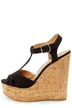 """Soda Path Black Cotton T-Strap Platform Wedge Sandals: Start your trek down the path to style nirvana with these sandals. Black canvas upper has a layered peep toe vamp with side cutouts, and a classic T-strap that fastens at the quarter with a silver buckle. Cork-wrapped platform builds from 1.5"""" at the vamp, to a 5.5"""" wedge heel. Cushioned insole. Non-skid felted rubber sole. $29"""