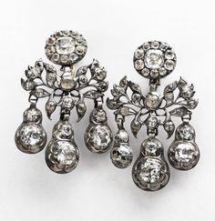 """Girandoler/örhängen. Örhängen och broscher med en rosettformation överst, därunder bladverk och slutligen tre hängande kläppar, kallas """"girandoler"""". Ordet kommer från franskan och betyder kandelaber, en stor ljusstake. Diamanter, fasettslipade bergkristaller eller glasstenar blev några av de mest omtyckta smyckestenarna under rokokotiden. Girandolerna på bilden är av silver och bergkristall, från 1700-talets mitt. Foto: Mats Landin, © Nordiska museet"""