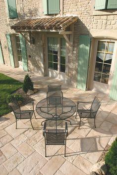 Quelques dalles, une façade imitation pierre et une table pour savourer le Soleil entre amis.