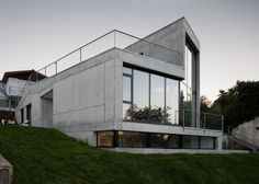 A wall of windows fronts this angular concrete house.