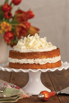 Mixed with fresh orange zest, ginger, and cardamom, this Orange-Scented Carrot Layer Cake is stacked between depths of White Chocolate Cream and crowned with wispy white chocolate curls.