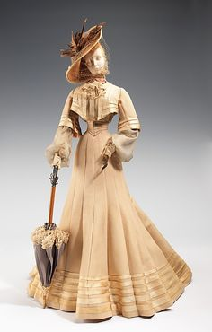"""""""1902 Doll""""  Robert Piguet (French, born Switzerland, 1901–1953)  Designer: Paulette (French)   Designer: Vedrenne (French) Designer: Fernand Aubry (French) Date: 1949   Culture: French   Medium: metal, plaster, hair, silk, straw, cotton, feather, wood Dimensions: 31 1/2 x 14 in. (80 x 35.6 cm)   Credit Line: Brooklyn Museum Costume Collection at The Metropolitan Museum of Art, Gift of the Brooklyn Museum, 2009; Gift of Syndicat de la Couture de Paris, 1949"""