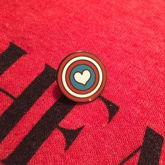 """Are+you+low+key+Cap+trash?+Then+this+pin+might+be+juuuust+up+your+alley.+It's+super+cute+and+little+and+just+baaaarely+there!+The+Heart+Shield+pin+is+an+ENAMEL+pin+that+measures+at+just+about+.75""""!+All+cute+and+ready+to+don+your+bag,+jacket,+or+whatever+you+can+(safely)+pin+this+thing+on.  PLEA..."""