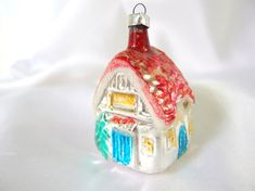 This vintage Christmas ornament was made in a blow mold. The silver, aqua and red house / cottage ornament has a red roof outlined in white mica, warm yellow windows and green pine trees on the front and back. Side door exit, too!  It measures 2.75 inches (7 cm) tall, not including hanging loop.  Condition: Mica is thinning. Check here for more colorful ornaments: http://www.etsy.com/shop/bythewaysidexmas?section_id=118867891  Thanks for looking! I am happy to answer questions! Jaci…