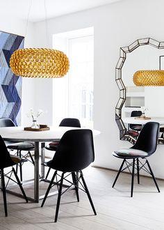 Poul Kjærholms runde marmor spisebord (PK54)  tilsat sorte Eames stole med velourpuder i forskellige farver fra Christina Lundsteen.  Caboche pendel fra Foscarini, et stort vægquilet samt et antikt spejl