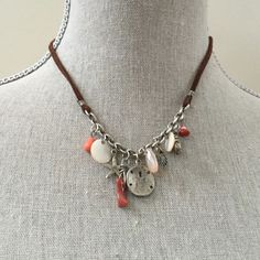 Coastal Charm Neclace Cute antiqued silver chain and brown suede cord necklace. Lobster claw clasp. Ten charms: coral shade beads, sand dollar, clam and scallop shells, starfish, coral and pearlized discs. Pristine. Comes with jewelry pouch. Jewelry Necklaces