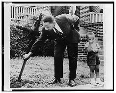 Martin Luther King, Jr., pulls up cross that was burned on lawn of his home, as his son stands next to him, 1960