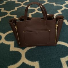"NWT! Ann Taylor Mini Signature Tote Brand new! Worn as a crossbody or a tote, this richly pebbled style polishes off a look with marvelously modern zipper detail. Magnetic snap closure. Two carry handles with 4"" drop. 42"" removable shoulder strap. Functional side zippers with gusset. Front welt pocket. Interior zipper pocket. 12""W x 8""H x 4""D. Ann Taylor Bags Mini Bags"