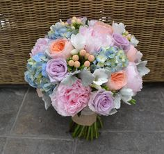 Stunning bouquet featuring pink Peonies, apricot David Austin Roses, Lilac Roses, peach Hypericum Berry, blue Hydrangea, ivory Freesia and Dusty Miller.