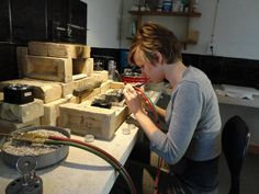 """Fire Bricks for Soldering Station: """"...Standard working height of the bench pin at a goldsmithing bench. Soldering..needs to be done seated, with forearms braced on the edge of the bench. This picture of Miranda is a great example; she is a professional goldsmith at work with perfect form. You can tell she is sitting flat footed on the floor, her posture is good, and because of those aspects she is focused and concentrating, her control is excellent."""" (Michael David Sturlin)"""