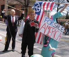 GW Bush, Worst President EVER. Shown here with his puppetier Dick Cheney. Peace activist Kelly Jacobs, dressed as Miss America is waving a peace flag and For Sale America sign. These Bush administration protesters were participating in a peace march in Birmingham Alabama.