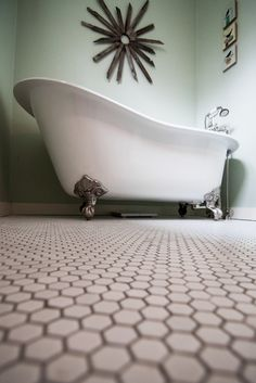 A closer look at the tub's ornate claw-foot detailing. We think it's a perfect match with the old-fashioned penny tile floor.