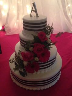 4 tired cake decorated with black stripes and decorated with a cascade of hot pink roses, Gerbera Daisies and white spray roses. Cake designed by Flowers by the Bunch
