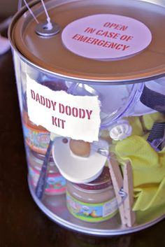 For a new dad-to-be make a Daddy Doody Kit: diapers, cream, gloves, goggles, mask, clothes pin, hand sanitizer, baby wash, cloth, baby food, spoon, wipes, pacifier, Tylenol.