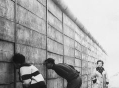 Berlinenses ocidentais espiam nos espaços entre o muro o lado oriental da capital  Foto: Getty Images