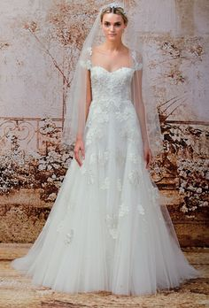 Brides.com: Monique Lhuillier - Fall 2014. Lace and tulle A-line wedding dress with sheer cap sleeves and lace applique details, Monique Lhuillier