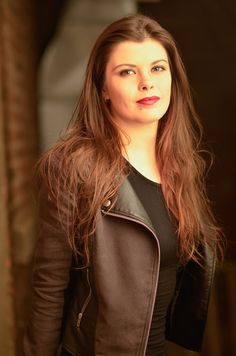 Portrait of young woman with brown hair along a red brick wall in a leather jacket