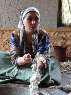 Woman Displays Silk Cocoons for Spinning. Margilon - Uzbekistan