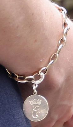 HRH the Duchess of Cambridge wearing a gold bracelet with her cypher on one side (the side shown on the picture) and the Duchess of Cornwall's cypher on the opposite side.
