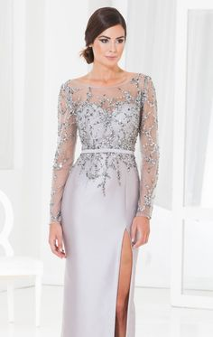 Show off your natural beauty in Terani Couture Evening M3846. This glamorous evening gown is made of satin. The fitted bodice features a sheer high neckline with sheer long sleeves and a sheer v shape back. Beads adorn the bodice and sleeves while a matching sash highlights the waist to complete the style.