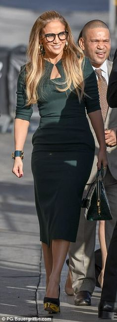 Stylish: Lopez, 48, poured her curves into a dark green dress that featured a bolero jacke...