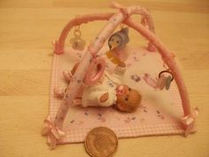 Miniature baby playing on activity mat. In 1/12 scale.