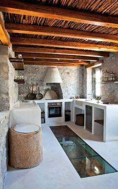 Cozinha rústica com móveis de alvenaria e chão de vidro com vista para adega