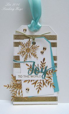 supplies: white and Audrey blue cardstock, gold metal foil, aqua glitter cardstock, Wplus9's Stitched tags, Simon's Nautical Borders (stripes), Penny Black Snowflake Trio snowflake dies, Wplus9's Hand-lettered Holiday die and matching stamp set. Ranger super fine detail gold embossing powder, aqua ribbon, gold stretchy twine, gold sequins