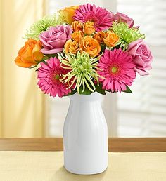 Captivate your senses with this truly original Vibrant Blooms Bouquet, featuring purple and orange roses, multi-bloomed orange spray roses, cheery hot pink Gerberas and alluring green Fuji mums, in a unique milk pint vase.