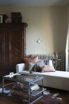 Traditional - An iron and glass coffee table, linen closet, and upholstered chaise in the corner of a bedroom
