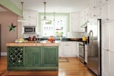 A dark green wash on the island adds balance to this kitchen's pastel walls and cream-colored cabinets. Sherwin-Williams Bonsai Tint (walls); Cottage in Maple with Kale stain (island), Brighton Cabinetry from cabinetdiscounters.com | Photo: Helen Norman